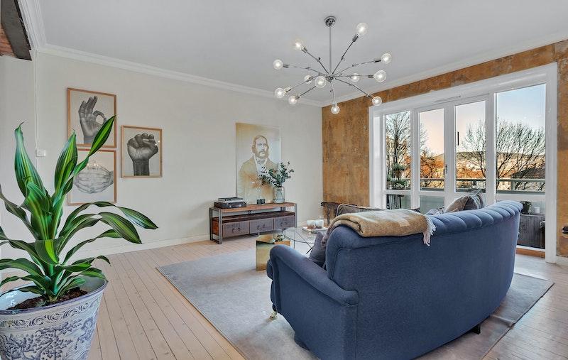 Stue med flott utsyn. Lysinnslipp fra store vindusflater ut mot balkong