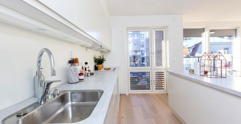 Kjøkkenet er utstyrt med 40mm laminatbenkeplate i modellen Hvit Betong fra Sigdal, underlimt stålvask, ettgreps armatur, slimline ventilator.
