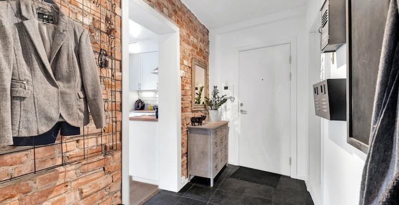Det rustikke preget i hall/entré gir en tøff kontrast til resten av leiligheten