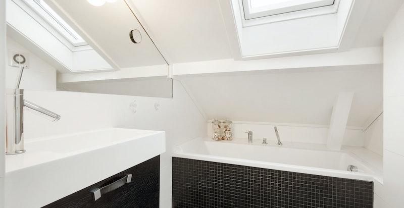 Stilrent bad på loft med badekar og wc.