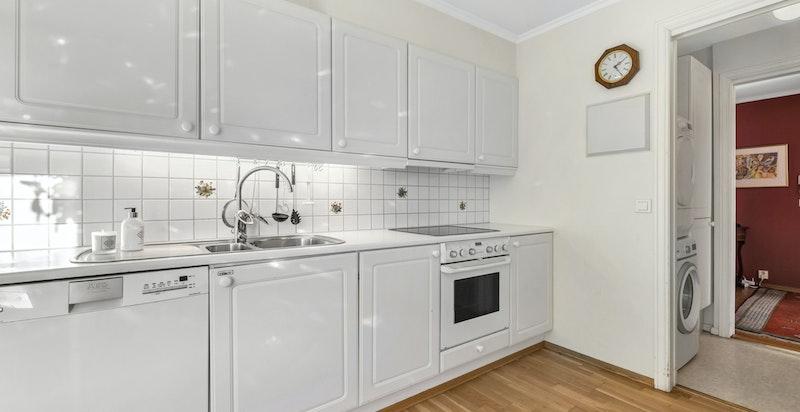 Hvit profilert kjøkkeninnredning med stekeovn og koketopp