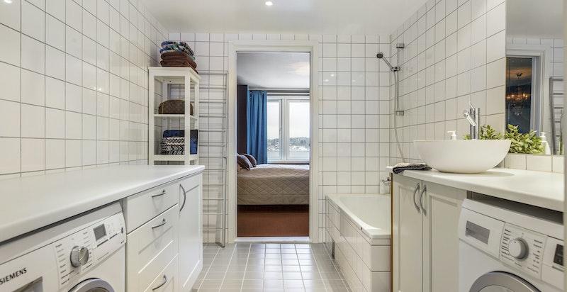 Romslig bad/ vaskerom med innfliset badekar