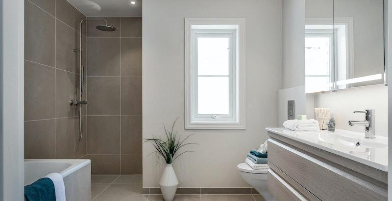 Stort og tidsmessig hovedbad m/ badekar og romslig dusjsone (dusjdør i herdet glass kommer)