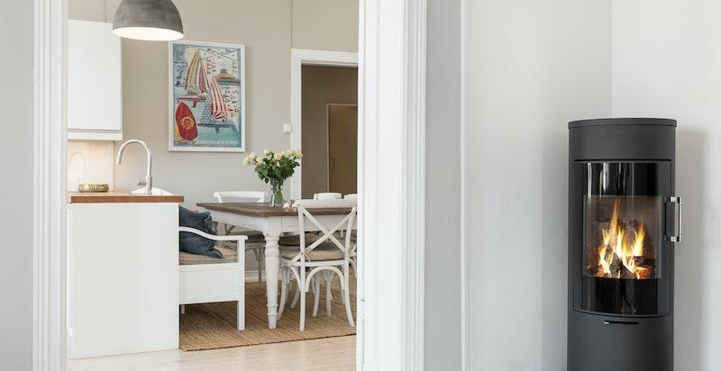 Ildsteder med moderne peisovn i stue og kamin på spisekjøkken