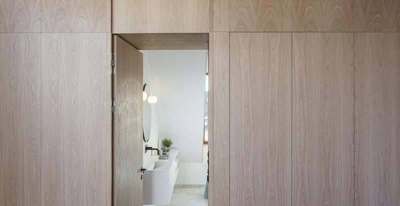 Lekker vegg i eikefinish med skap og lagring sett fra heisen med adkomst til soverom og bad