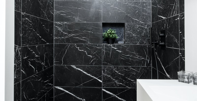 Bad i tilknytning til hovedsoverom med sorte fliser i marmor, tapwell armatur og Corian benkeplate