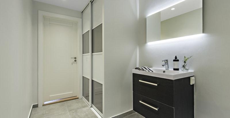 Praktisk bad med plass til vaskesøyle i skyvedørsgarderobe