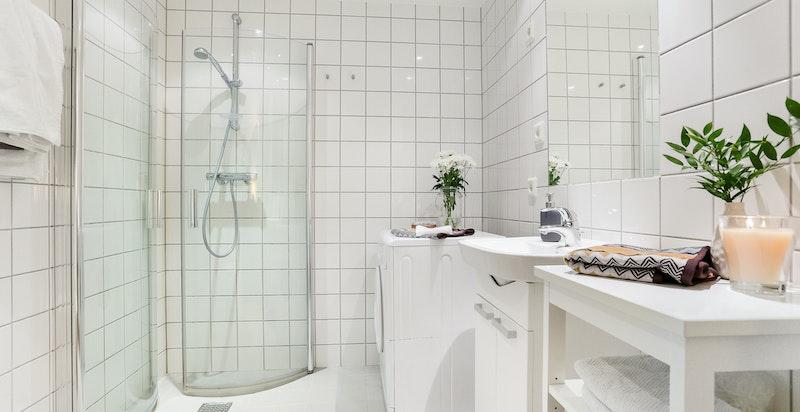 Pent bad med dusjhjørne og opplegg for vaskemaskin og tørketrommel