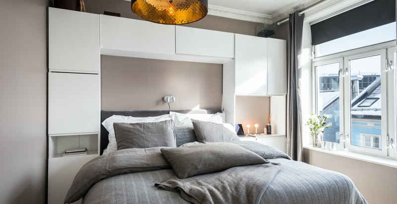 Et svært delikat soverom på innsiden av stuen med garderober for oppbevaring.