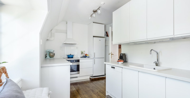 Pent og praktisk kjøkken med integrerte hvitevarer.