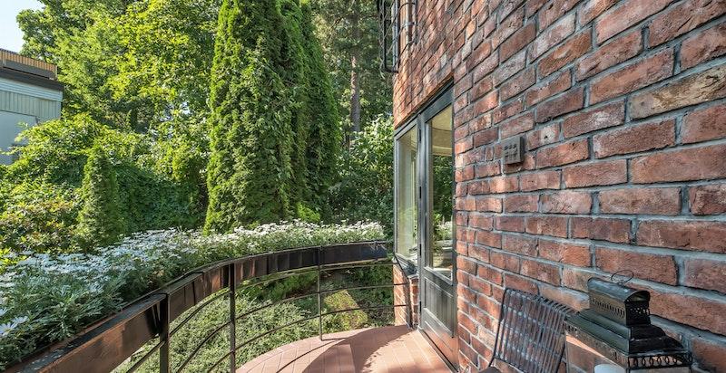 Balkongen er skjermet og solrik med hyggelig utsyn mot den flotte hagen
