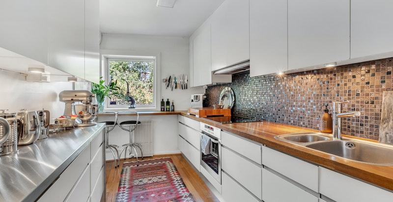 Kjøkken med innredning fra 2005 som består av glatte fronter med integrerte håndtak, to stålkummer med blandebatteri, heltre og stål benkeplater