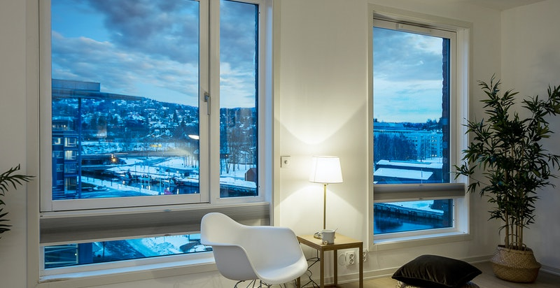 Store vindusflater med utsikt mot fjorden, kveldssolen kommer også inn i leiligheten