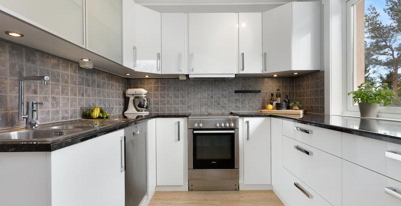 Velutstyrt kjøkken med fliser over benk og godt med skapinnredning