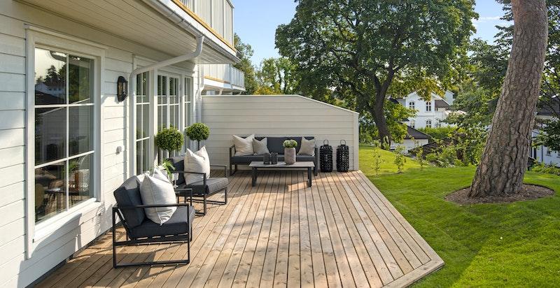 Romslig vestvedt terrasse og opparbeidet gressplen