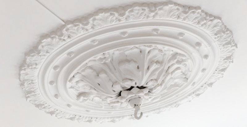 Klassiske detaljer med stukkatur og rosett i himling.