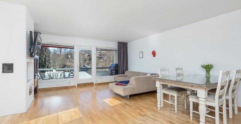 Stue med peis, store vindusflater og adkomst til balkong