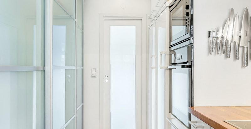 Kjøkkenet er praktisk designet med rikelig benke- og oppbevaringsplass, samtidig som det er plass til spisebord i rommet.