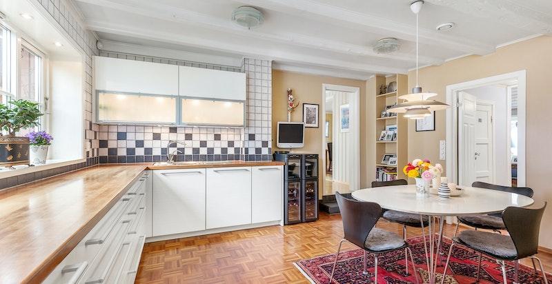 Stort og innholdsrikt kjøkken med parkettgulv og lysmalte flatrer i en varm tone.