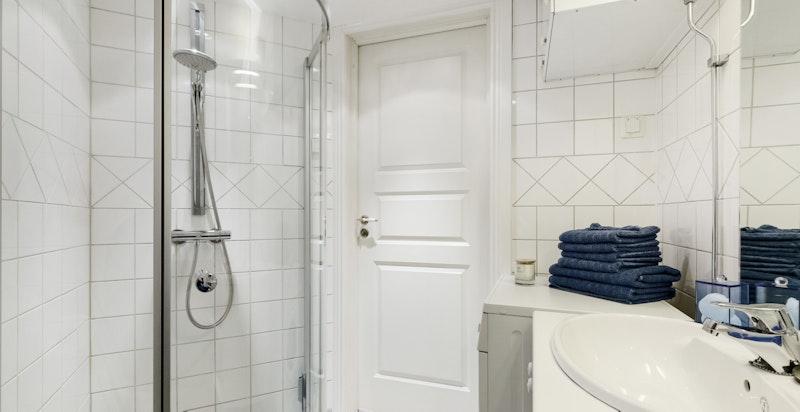 Bad II er utstyrt med baderomsinnredning med servant, vegghengt baderomsskap, speil over servant, veggmontert dusj med dusjvegger, frittstående toalett.