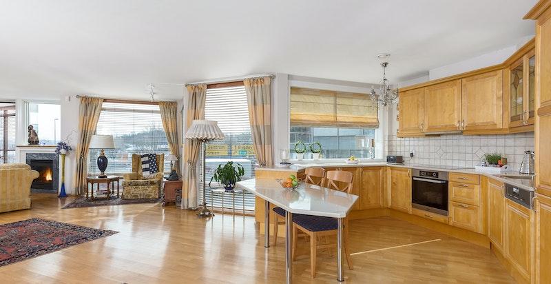 Stort og innholdsrikt kjøkken med profilert heltre front, corian benkeplate i hvit utførelse og lyse fliser over benk.