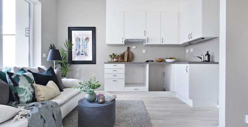 Det er åpen løsning mot moderne, tidløst og praktisk designet kjøkken med god benke- og lagringsplass i L-form.