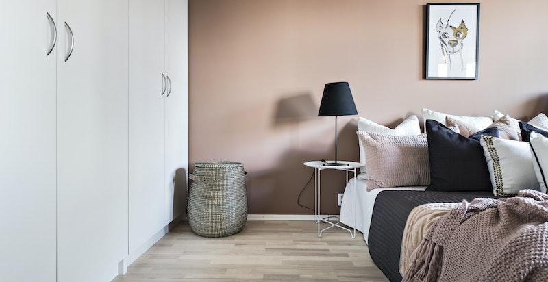 Rommet er innredet med romslig garderobeinnredning og har skyvedører på hver sin side av sengen.