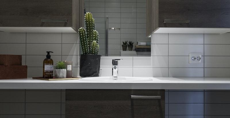 Badet er utstyrt med veggmontert toalett, dusjhjørne med innfellbare dører i herdet glass, samt opplegg for vaskemaskin og tørketrommel under benkeplaten.