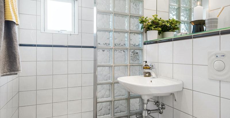 Dusjhjørne separert ved glassbyggersten. Vegghengt wc, speil med overlys og hylle med glassplate.