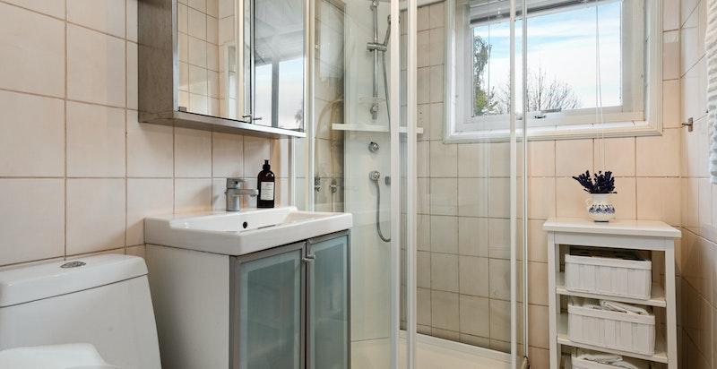 Eldre baderom innnredet med dusjkabinett, servantskap og toalett. Flislagt gulv med varmekabler og flislagte vegger.
