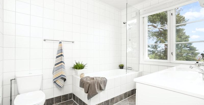 Delikat, flislagt bad med innfliset badekar