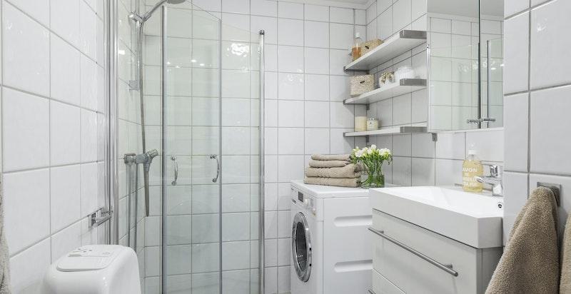 Flislagt bad med dusjhjørne, wc, servant og opplegg til vaskemaskin og tørketrommel.