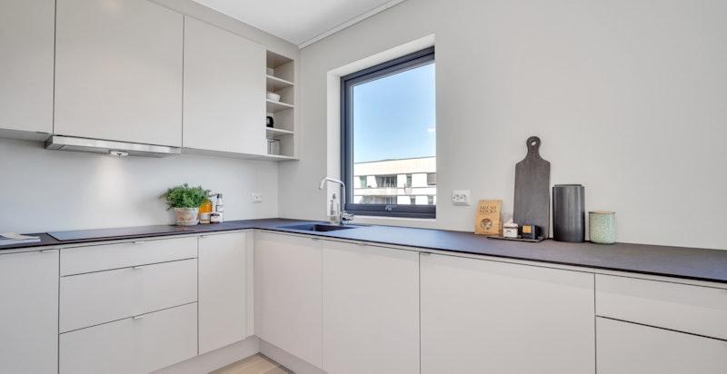 Moderne kjøkken fra Sigdal med integrerte hvitevarer. Lyst og flott med vindu.