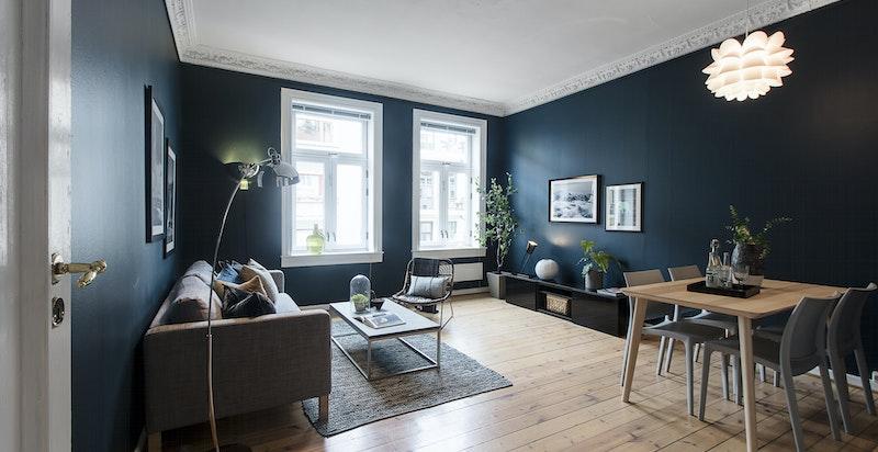 Leiligheten har en romslig stue med plass til både langbord og sofagruppe.