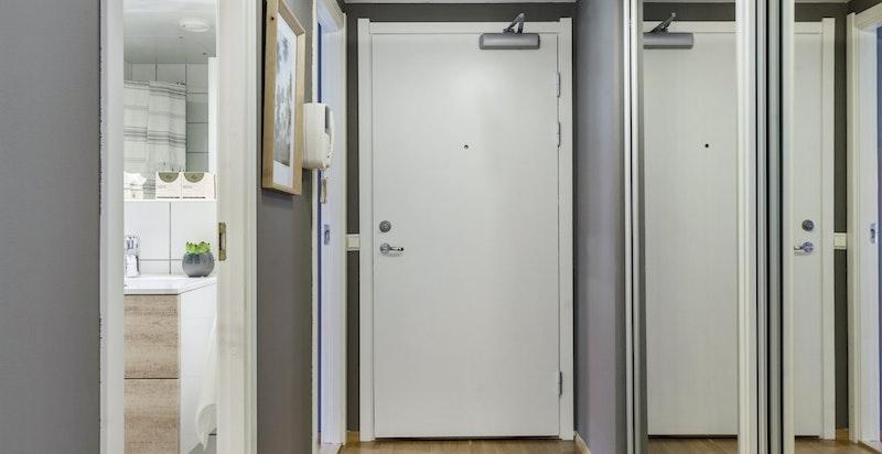 Skyvedørsgarderobe med speil i entreen er med på å maksimere romfølelsen.