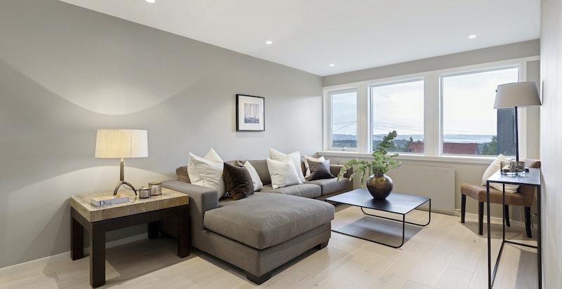 Stor kjellerstue med store vinduer som slipper inn mye naturlig lys.