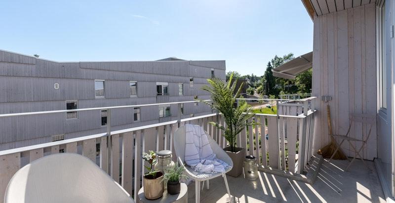 Romslig balkong med optimale solforhold. Liten lagringsbod ses til høyre.