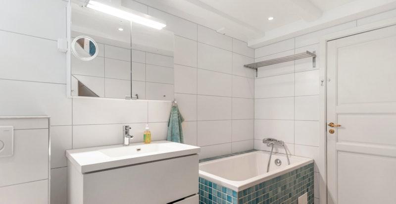Flislagt stort baderom med badekar, dusj og wc