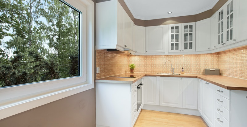 Pen kjøkkeninnredning med heltre benkplate. avtrekksvifte og integrerte hvitevarer.