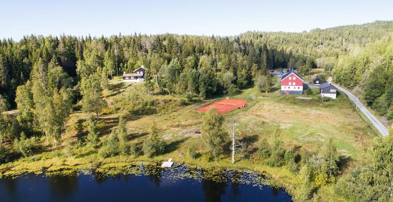 Eventyrlig eiendom på ca. 95 mål med flere bolighus og gjestehus, låve, stabbur, garasje, tennisbane og eget skogstjern