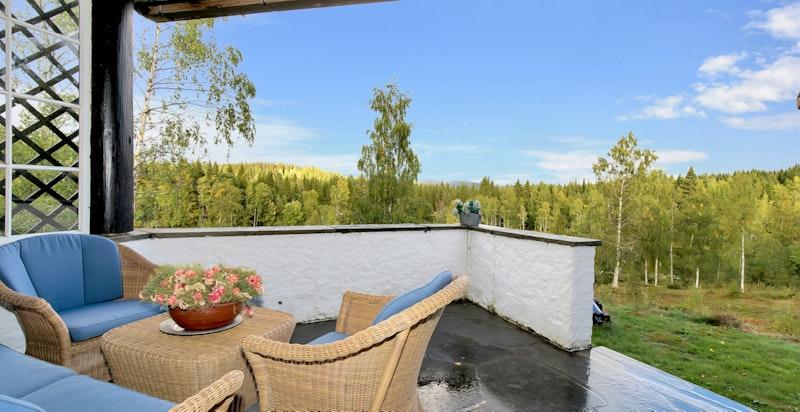 Overbygget terrasse med vid utsikt over skogskledde åser og Langebrutjern