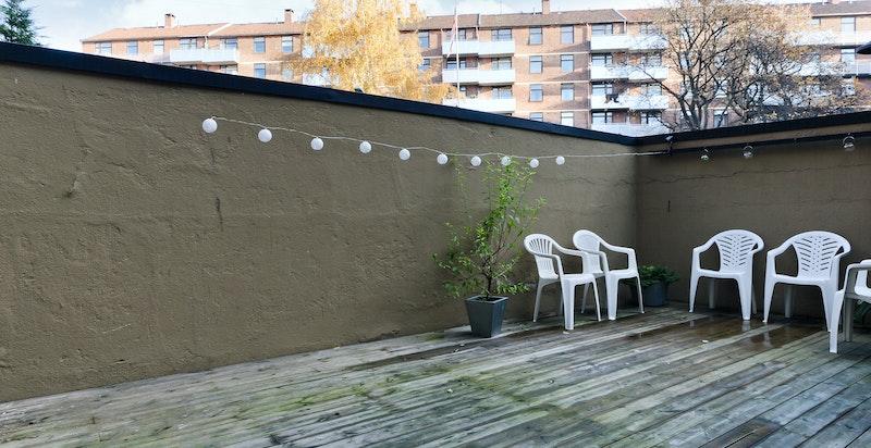Opparbeidet bakgård med sittegruppe, grill og sykkelparkering.