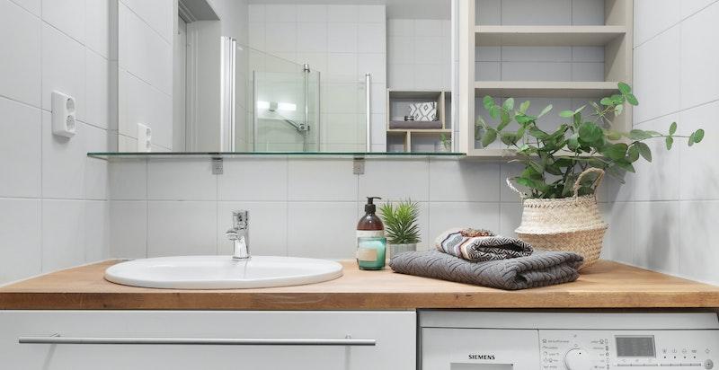 Fin heltre benkplate med servant og stort speil over, samt montert vaskemaskin under, ved siden av gode skuffer for oppbevaring.