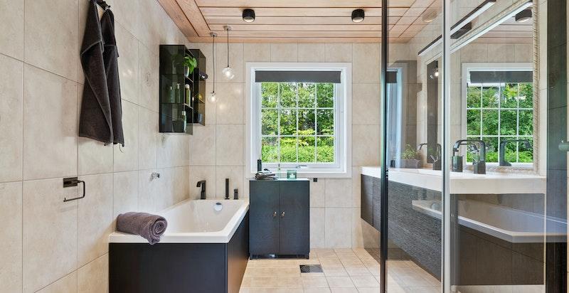 Baderommet er romslig og inneholder både badekar og dusjhjørne.