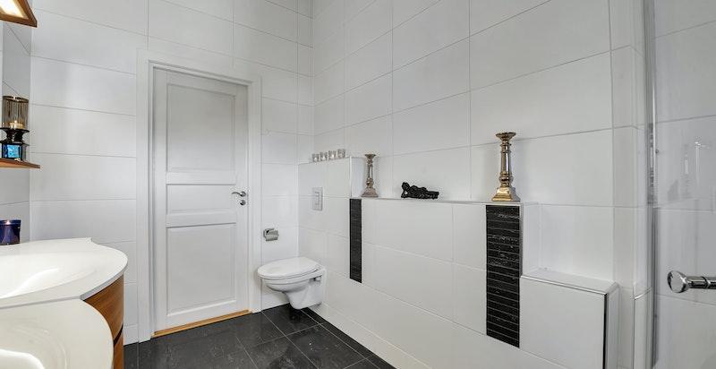 Bad/wc med dusjhjørne med innfellbare dusjdører, veggmontert toalett, ventil i himling, to servanter med underskap og blandebatteri
