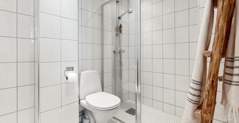 Badet har dusjhjørne med dusjvegger i glass.