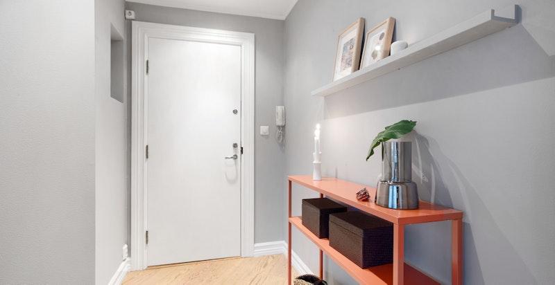 Lys og innbydende entré med delikat malte vegger og eikeparkett på gulvet. Entréen har god plass til å henge fra seg ytterklær og sko. Entréen gir et godt førsteinntrykk for resten av leiligheten. Dørcalling og branndør med smekklås.