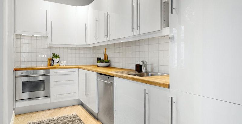 Tidsriktig kjøkken med innredning i høyglanslakkerte, glatte skapdører og skuffefronter. Det er godt med skap- og benkeplass.