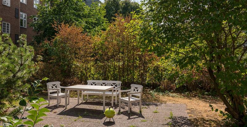 Fellesområde i sameiet med hage og sittegrupper.