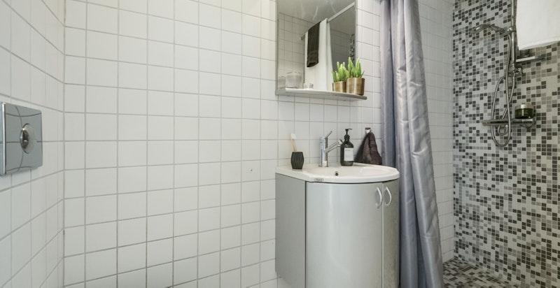 Pent badeværelse med dusjnisje, toalett og servantskap.